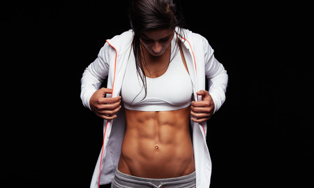 slim tummy: Portrait of young woman looking at her muscular abs. Fitness model on black background