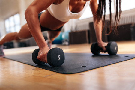 body conscious: Cropped shot of muscular woman doing pushups on dumbbells. Female exercising on fitness mat at gym.