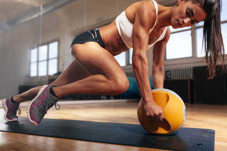physical: Muscular woman doing intense core workout in gym. Strong female doing core exercise on fitness mat with kettlebell in health club. Stock Photo
