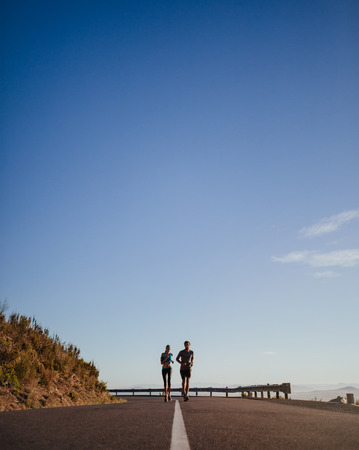 open country: Distant shot of two young runners running on open country road with blue sky. Two young man and woman jogging outdoors on a summer morning.