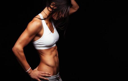 sexo femenino: Imagen del modelo de mujer joven en ropa deportiva de pie en el fondo negro con copyspace. Mujer con el torso musculoso de pie con las manos en las caderas. Foto de archivo