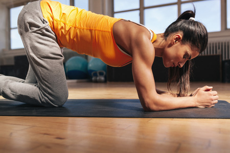 gym workout: Young woman exercising on fitness mat. Strong young female athlete doing core workout in gym. Stock Photo