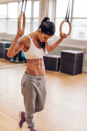 Fit young woman exercising with gymnastic rings. Muscular woman at gym looking down, preparing from training session.