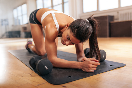 tired: Young woman relaxing after doing pushups, woman exercising on fitness mat with dumbbells in gym. Stock Photo