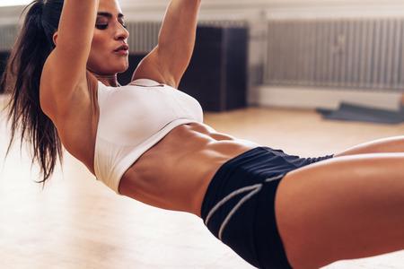 muscular: Recorta la imagen de mujer joven del ajuste que ejercita en el gimnasio. Mujer muscular va pull-ups con anillos gimn�sticos.