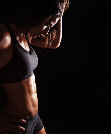 Portrait of young woman in sports bra relaxing after her workout on black background with copyspace.