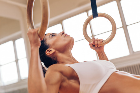 pullups: Close up shot of strong young woman doing pull-ups with gymnastic rings. Fitness female athlete exercising at gym.