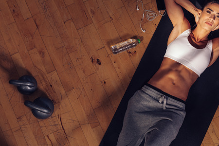 Top view of fitness model lying on exercise mat. Overhead shot of fitness instructor tired resting on mat with water bottle, mobile phone and kettle bell on floor.