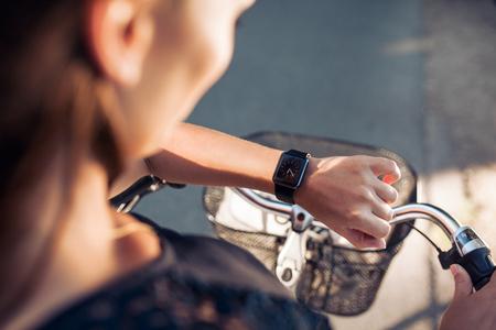 cerrar: Mujer con una bicicleta mirando su SmartWatch. Cierre de tiro de tiempo de verificación de sexo femenino en su reloj de pulsera inteligente.