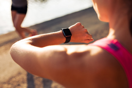 checking time: Close up shpt of sportswoman looking at her stopwatch. Jogger checking time on her smartwatch.