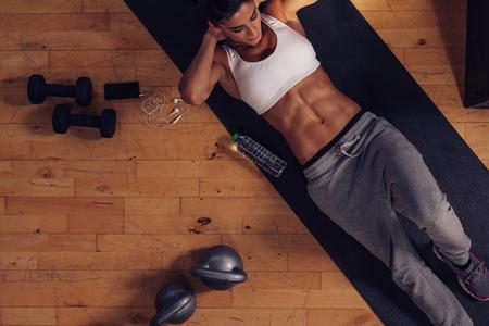 muscular: Joven deportiva tendido en estera de ejercicio haciendo abdominales. Vista superior de la mujer muscular que hace abdominales abdominales en el gimnasio. Foto de archivo