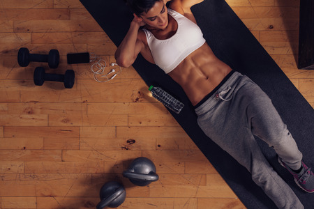 lying on stomach: Sporty young woman lying on exercise mat doing sit-ups. Top view of muscular woman doing abs crunches in gym.