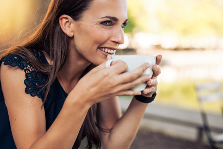 drink coffee: Young woman holding a cup of coffee and looking away smiling. Caucasian female drinking coffee at cafe. Stock Photo