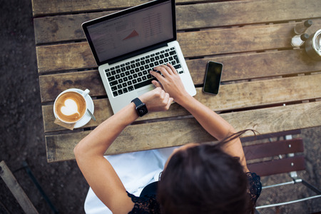 outdoor cafe: Overhead view of young woman checking time on her smartwatch while working on her laptop at a cafe. Top view shot of female sitting at a table with a cup of coffee, laptop and mobile phone. Stock Photo
