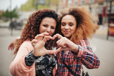 finger shape: Happy young female friends making heart shape with hands and fingers. Two women standing together outdoors on city street. Focus on hands.