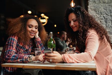 dos personas hablando: Retrato de mujeres jóvenes sentados en un café usando el teléfono móvil. Dos chicas jóvenes que leen un mensaje de texto en el teléfono móvil. Foto de archivo