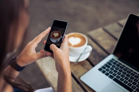 capuchino: Mujer que toma una foto de una taza de café con su teléfono inteligente mientras está sentado en una cafetería.