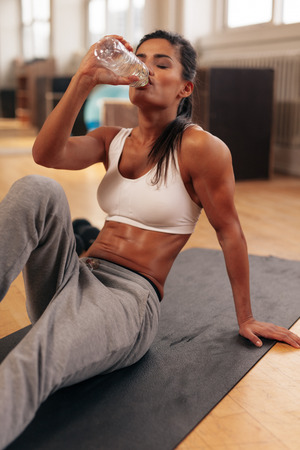 taking a break: Fit young woman drinking water in the gym. Muscular woman sitting on exercise mat. Fitness female taking break after exercise. Stock Photo