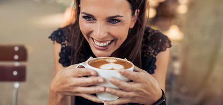 women coffee: Close up shot of cheerful young woman drinking coffee at a cafe and looking away. Caucasian female enjoying a cup of coffee.