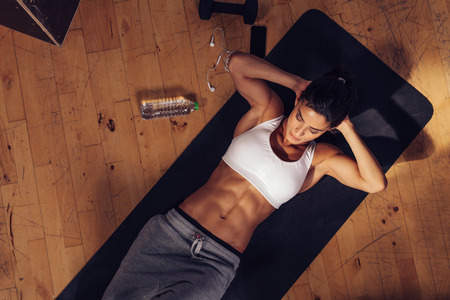 スポーティな若い女性がジムで腹筋を行うことのヨガマットの上に横たわる。腹筋のクランチを行う筋肉女性の平面図です。