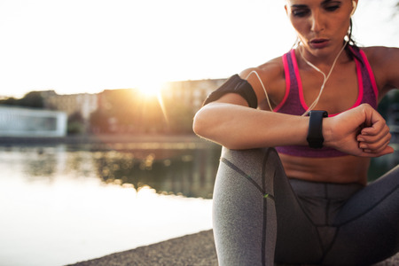 corriendo: Joven y bella mujer sentada al aire libre usando un SmartWatch para monitorear su progreso. Corredora de raza cauc�sica descanso y comprobar su rendimiento en la aptitud dispositivo reloj inteligente.