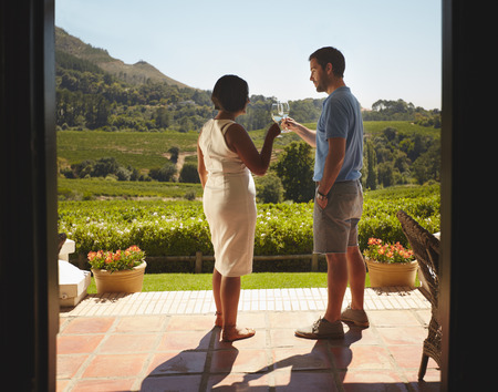 wineries: Young couple toasting wine while standing outdoors at winery restaurant patio. Man and woman on vacation celebrating with wine. Stock Photo