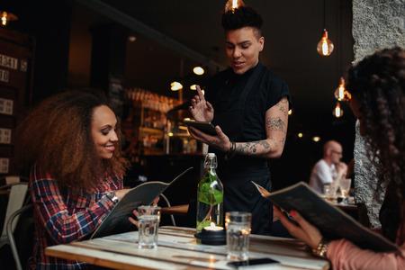 meseros: Felices los jóvenes que se sientan en el restaurante de leer la tarjeta del menú y dando órdenes al camarero masculino, mientras camarero poniendo fin a una tableta digital. Foto de archivo