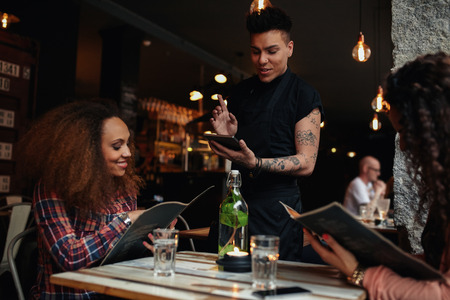 Happy young people sitting in restaurant reading menu card and giving orders to the male waiter, while waiter putting order onto a digital tablet.
