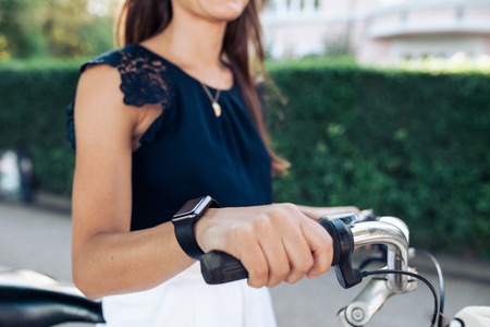 woman hands up: Woman riding a bike with a smartwatch. Female wearing smart watch while cycling. Stock Photo