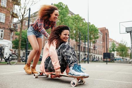 women: Chica joven feliz que se sienta en longboard siendo empujado por su amiga. Las mujeres jóvenes disfrutando de patinaje al aire libre.