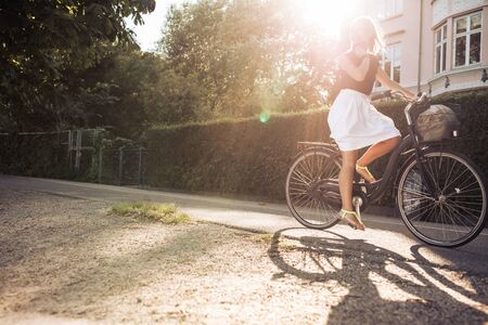 young tree: Outdoor shot of a young woman cycling on street. Female riding bicycle with sun flare. Stock Photo