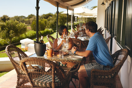 food and drink: Young couple enjoying a glass of wine. Man and woman on holiday drinking wine at winery restaurant.