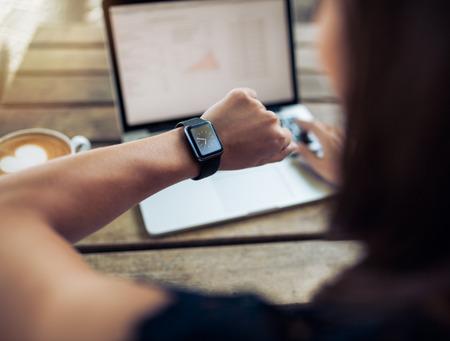 Tiempo: Cierre de tiro de una mujer que controla el tiempo en su SmartWatch. Mujer sentada en el café con un ordenador portátil y una taza de café. Foto de archivo