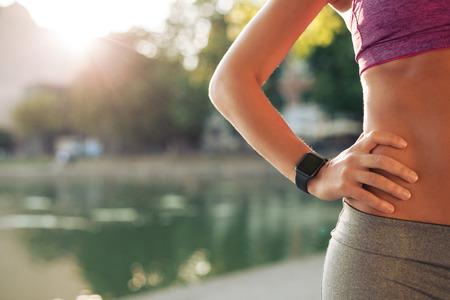 fitness: Sportswoman indossare dispositivo SmartWatch. ritagliata colpo della donna di misura in abbigliamento sportivo in piedi con la mano sul fianco all'aperto, con il chiarore del sole.