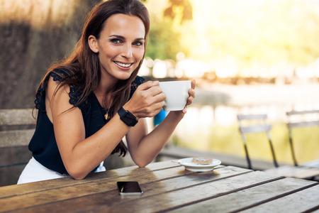 Retrato de la hermosa mujer joven sentada en una mesa con una taza de café en la mano mirando a la cámara sonriendo mientras en el café. Foto de archivo