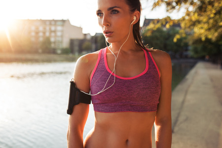 Young woman runner wearing armband and listening to music on earphones. Fit sportswoman taking a break from outdoors training. Banque d'images