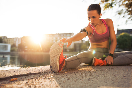 Fitness woman stretching before a run. Young female runner stretching her muscles before a training session. She is sitting on sidewalk along a pond in city on a sunny day with sun flare. Banque d'images
