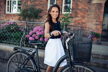happily: Beautiful woman riding a bicycle in city. Caucasian female smiling happily and looking at camera. Woman walking with a cycle.