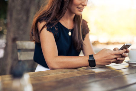 lifestyle: Žena psaní textové zprávy na chytrý telefon v kavárně. Oříznuté obraz mladé ženy sedící u stolu s kávou pomocí mobilního telefonu.