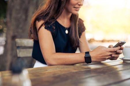 mujeres felices: Mujer escribiendo un mensaje de texto en el tel�fono inteligente en un caf�. Recorta la imagen de mujer joven sentada en una mesa con un caf� usando el tel�fono m�vil.