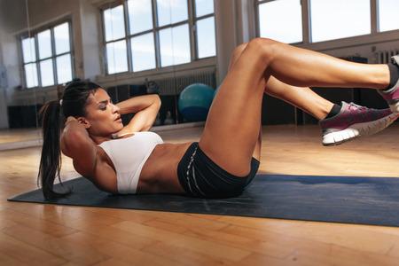 muscle: Mujer joven que hace pilates, trabajando en los m�sculos abdominales. Mujer de la aptitud de hacer ejercicio para mejorar la fuerza de la base muscular en el gimnasio.