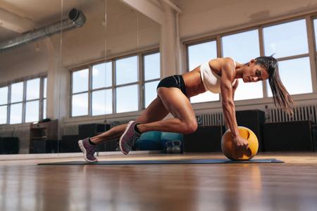 Porträtt av en passform och muskulös kvinna gör intensiv kärna träning med kettlebell i gymmet. Kvinna utövar på crossfit gym.