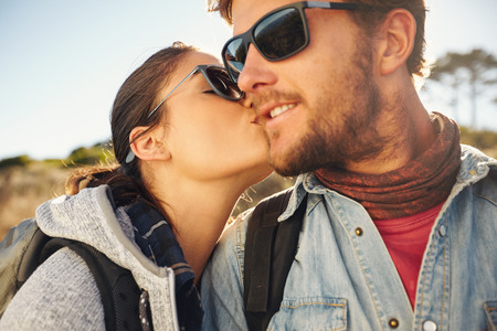 man woman kissing: Loving young tourist couple hiking. Young woman kissing cheek of her boyfriend, outdoors on a hike.
