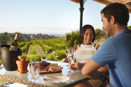 people: Happy young couple at winery restaurant with vineyard in background. Smiling young woman with a man sitting at table drinking wine. Stock Photo