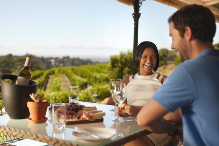 persona sentada: joven pareja feliz en el restaurante de la bodega con el vi�edo en el fondo. mujer joven con un hombre sentado en el vino de mesa sonrisa de consumici�n. Foto de archivo