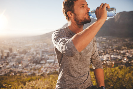 man drinking water: Young runner taking a break after morning run drinking water. Young man relaxing after a running training session outdoors in countryside on sunny day. Stock Photo