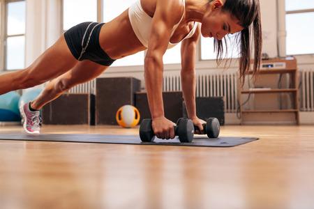 salud y deporte: Fuertes mujer joven haciendo flexiones ejercicio con pesas en la estera de yoga. Modelo de la aptitud que hace un intenso entrenamiento en el gimnasio.