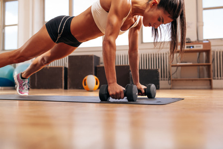 Strong young woman doing push ups exercise with dumbbells on yoga mat. Fitness model doing intense training in the gym. Stock Photo