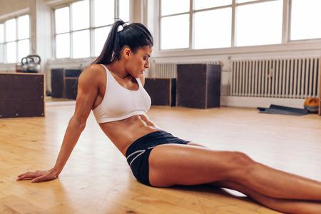 deportistas: Retrato de mujer joven musculoso relaja después de entrenamiento en el gimnasio. Atleta femenina Fit tomando un descanso del entrenamiento.