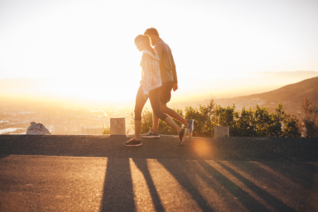 2 people: Couple walk along road at sunrise. Couple talking a walk on hillside road with bright sunlight. Stock Photo